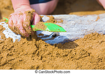 Playtime - Male person with dirty hand playing in the sand a...