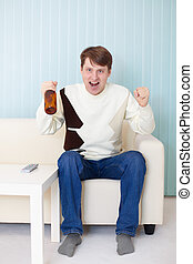 Football fan sitting on sofa with TV and beer