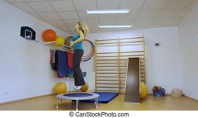 Young woman jumping on the trampoline in the gym