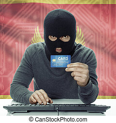 Dark-skinned hacker with flag on background holding credit...