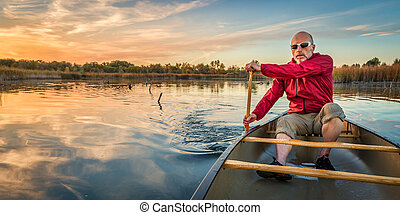 paddling canoe at sunset