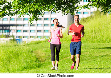 Fitness Friends running together through park