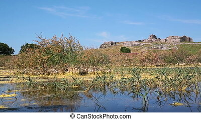 Swamp lake with ruins and mountain with ruins of ancient...