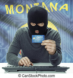 Dark-skinned hacker with USA states flag on background holding credit card - Montana
