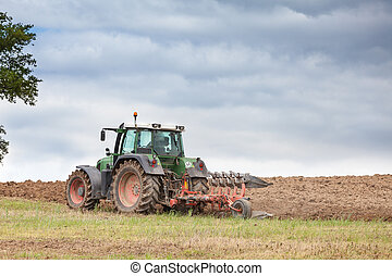 Farmer ploughing overwintered fields ready for planting the...