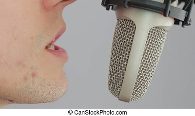 Man singing at studio microphone - Man expressive move,...