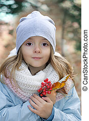 Small girl outdoor portrait.Child in autumn park with berries in hands.