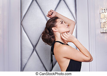woman in a black dress posing in the interior