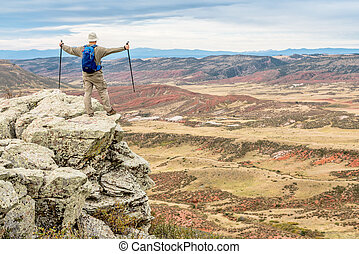 hiker on rocky cliff overlooking valley - male hiker...