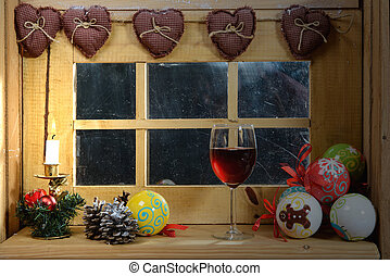 glass of red wine at the window, with a christmas decoration...