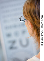 Woman reading from an eye test chart