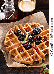 Whole wheat breakfast waffle served with blackberries and...