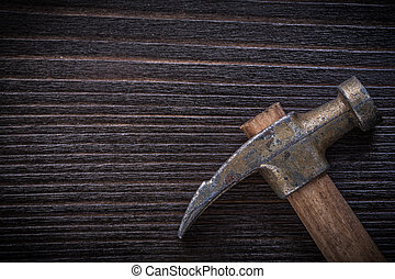Longstanding claw hammer on vintage wooden board...