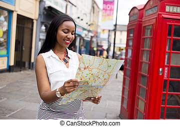 reading map - young tourist visiting London reading a map