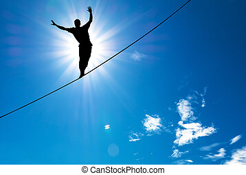 Silhouette of man balancing on the rope concept of risk...