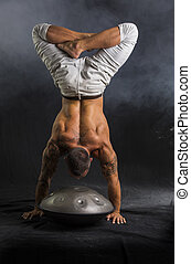 Male Drummer Doing Handstand on Steel Drum in Studio -...