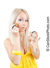 young woman putting make up on her face. Isolated over white