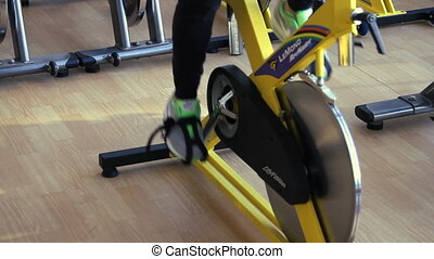 female exercising their legs doing cardio cycling training.