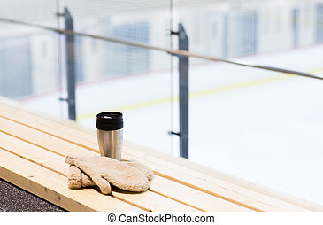 thermos cup and mittens on bench at ice rink arena - hot...