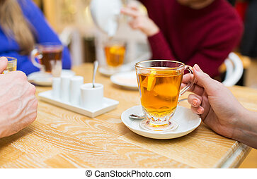 close up of female hand with tea cup at cafe - people,...