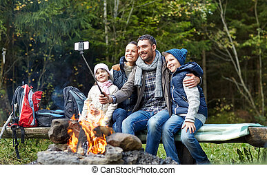 family with smartphone taking selfie near campfire -...