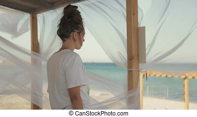 Young girl yogi meditating near the sea in the gazebo