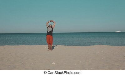 Yoga classes on the deserted ocean shore - Adult male doing...
