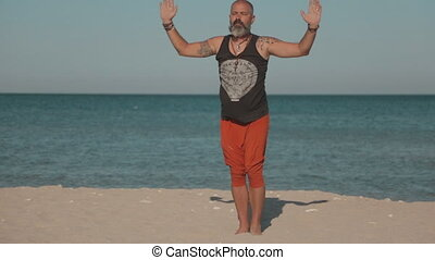 Man doing yoga near the sea