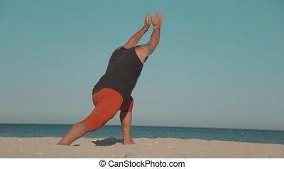 Brutal man practicing yoga at seashore - Brutal man...