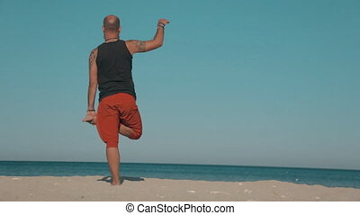 Yoga instructor demonstrates exercises of yoga on the beach...