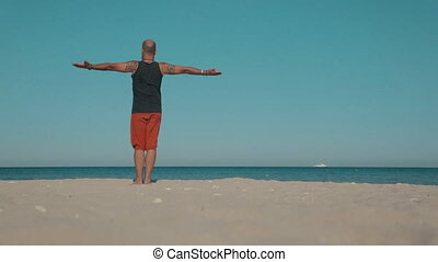Yoga instructor demonstrates exercises of yoga on the beach