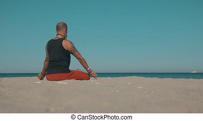 Man doing yoga on the shore of the beach - Man doing yoga on...