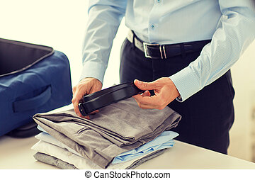businessman packing clothes into travel bag - business,...
