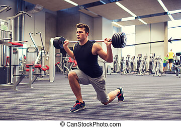 young man flexing muscles with barbell in gym - sport,...