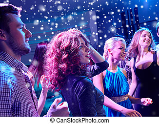 smiling friends dancing in club - new year party, holidays,...