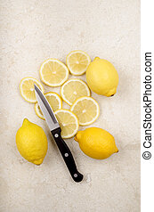 lemon, sliced lemons and a kitchen knife - fresh lemon,...