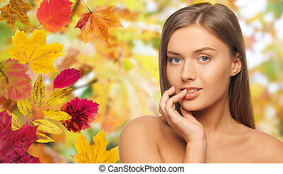 beautiful young woman face over autumn leaves - beauty,...