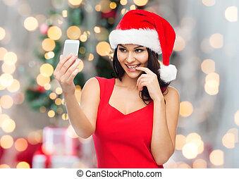 woman in santa hat taking selfie by smartphone - people,...
