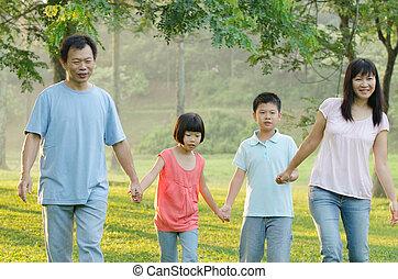 Happy Asian family walking