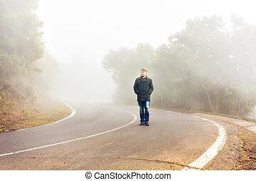 Man walking in a misty forest