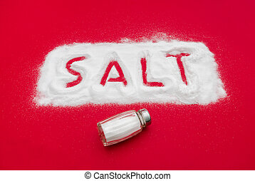 Salt shaker and text out of white powder on a red...