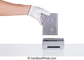 Hard drive in his hand is connected to the docking station. For saving data.