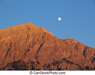 Moon over barren mountain