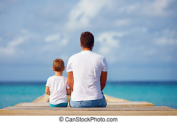 father and son sitting on pier near the sea