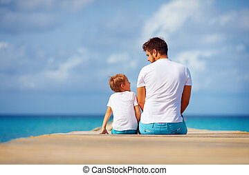 happy father and son sitting on pier and talk