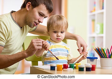 child boy painting in nursery at home - child boy with dad...