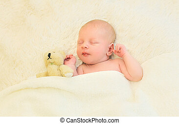 Cute infant sleeping together with teddy bear toy on the bed...