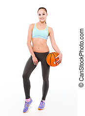 Sports woman holding basketball ball - Full length portrait...