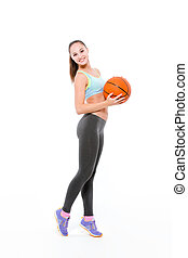 Sports woman posing with basketball ball - Full length...