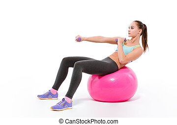 Woman doing exercises with dumbbells on fitness bal -...